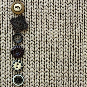 Row of Vintage Buttons Lined up on Soft Square Fabric Background